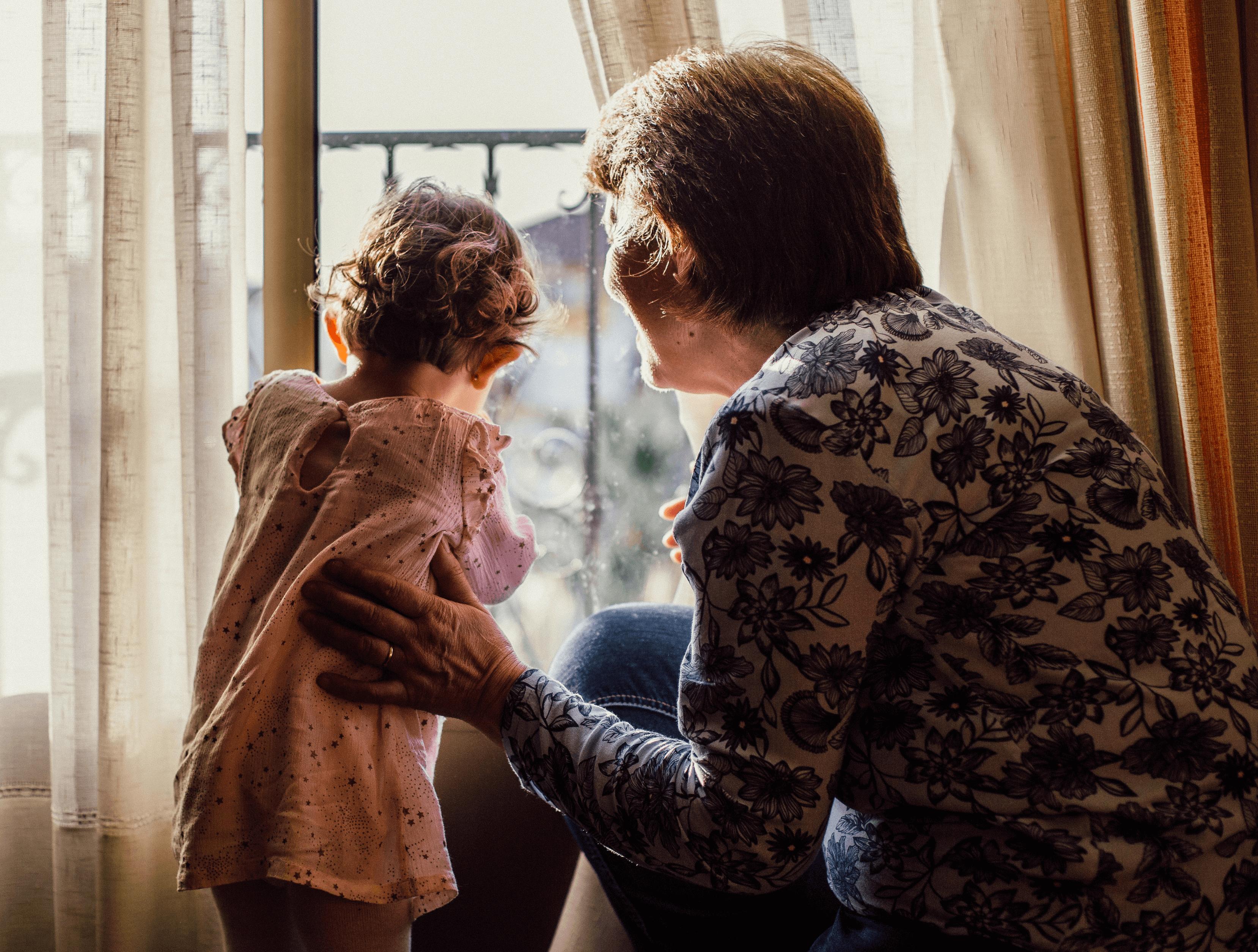 Grandparent holding child near window